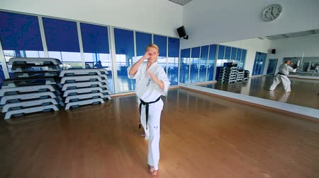 tanítvány : Young woman practicing the karate in the sports gym Stock mozgókép