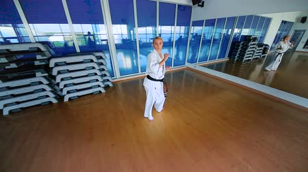blokkok : Young woman in white kimono practice the karate in the gym
