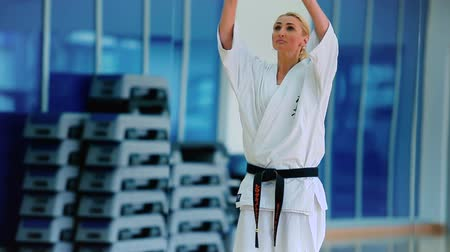 bloklar : Woman in white kimono practicing a few tricks in the gym Stok Video