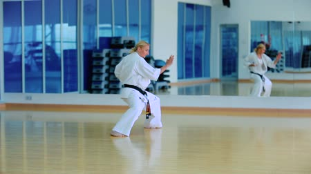 bloklar : Attractive woman show a karate trick with hands in the gym Stok Video