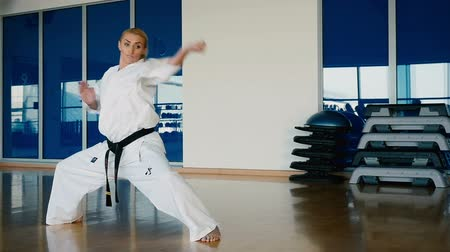 blokkok : Sporty blonde woman showing some karate tricks in the gym