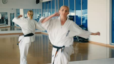 bloklar : Slowmotion womans karate trick near the mirror in the gym Stok Video