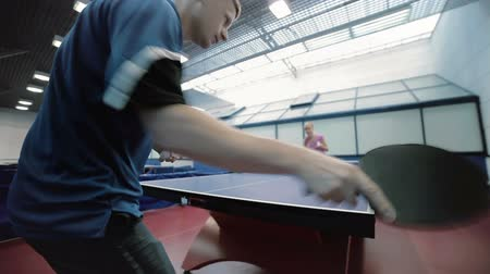 ракетка : Man in blue T-shirt playing a table tennis with woman at the court Стоковые видеозаписи