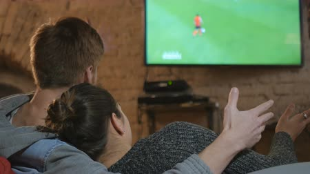 arka görünüm : Two young people watching football on TV