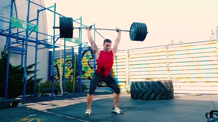 grapple : The sportsman training with heavy barbell on the sports ground Stock Footage