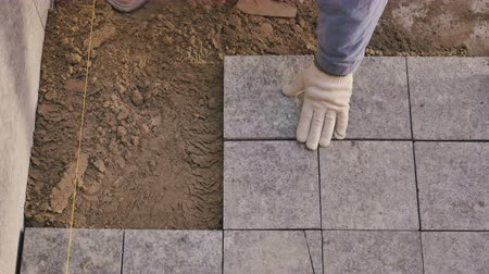 шпатель : Builder lays the tiles on the floor in house