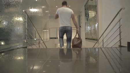 мышечный : Young man in white T-shirt down stairs in the hotel Стоковые видеозаписи