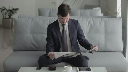 lounge : Young businessman is reading a newspaper and waits the boarding on the plane