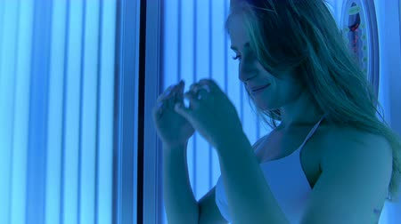 solarium : Pretty woman in white bikini posing for camera in the solarium Stock Footage