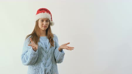 pained : Young girl in santas hat throws out the festive gift at white background