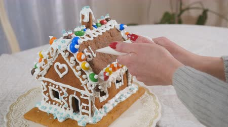 fırınlama : The woman writes a text with cream on the roof of gingerbread house