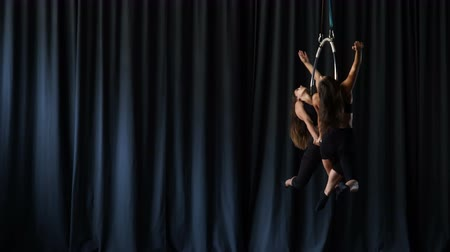 showbiz : Professional acrobats performs a gymnastic trick on the aerial hoop