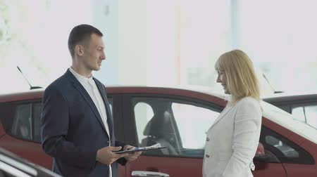 tratar : Happy businesswoman gets a car keys from salesman in car dealership Vídeos