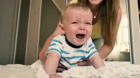 mudança : Mother comes to a crying baby to change his diaper