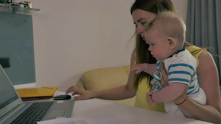 newborn child : Tired mother works with laptop with baby in arms Stock Footage