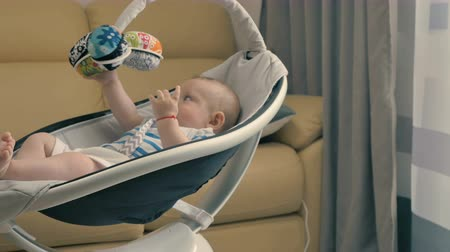 automatický : Cute little baby with dummy is rocking by the modern cradle