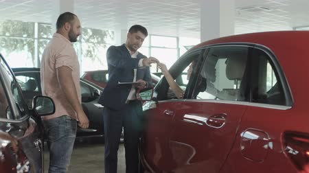 sprzedawca : The couple buys a new car in car dealership Wideo