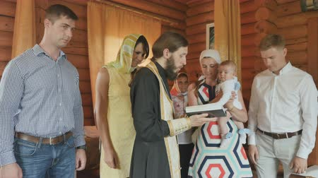 christening : A priest reads a prayer, parents and godparents listen; infant baptism ritual