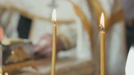 christening : Two holy candles, priest reciting the prayer from bible on blurred background Stock Footage