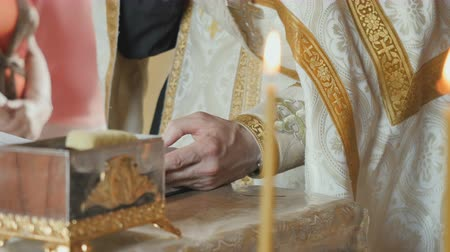 christening : The priest reciting the prayer from bible, two holy candles on foreground