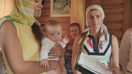 christening : Godmother holds a little boy in arms during baptism ritual