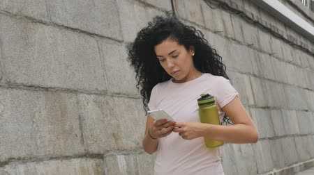 motivar : Pretty sportswoman uses phone and goes home after training