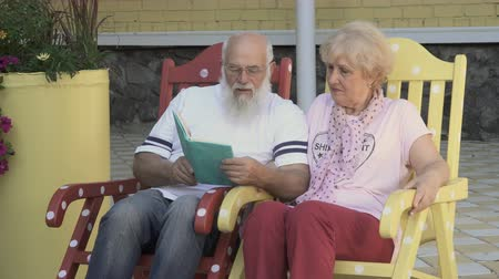 loved : Loved husband reads a book a beautiful wife, old people relax in rocking chairs