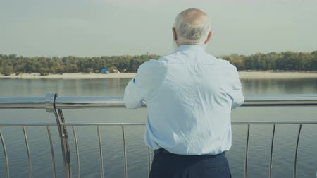 созерцать : Pleasant elderly man looks at the river