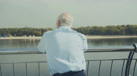 созерцать : Old gray-haired man looks at the beach near the river Стоковые видеозаписи