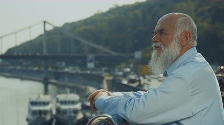созерцать : Old gray-haired man with beard relax near the river enjoying the view Стоковые видеозаписи
