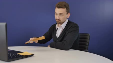 ameaça : Angry businessman threatens partners with a wooden ax during video conference Stock Footage