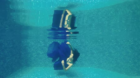 swimming underwater : Beautiful girl in long blue dress swims under water in swimming pool