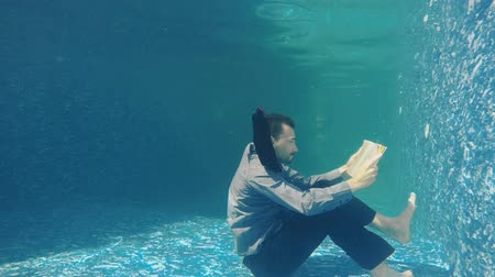alatt : Businessman in suit read book under water