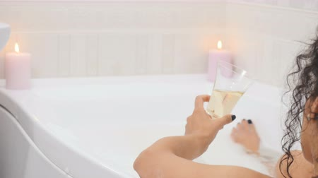 iğfal : Attractive woman takes bath with foam and candles and drinks champagne Stok Video
