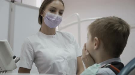 lékař : Little boy complains the dentist about toothache sitting in dentist chair