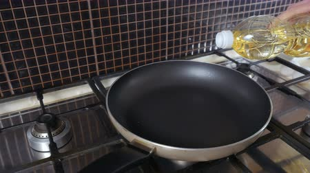 heating up metal : Woman pours oil at the frying pan Stock Footage