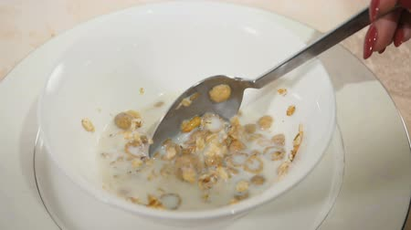 засахаренный : Female hand mixes with spoon muesli in a bowl Стоковые видеозаписи