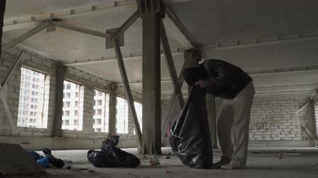 unlucky : Homeless searches something in garbage bag and throws out the trash from it Stock Footage