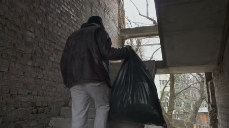 csavargó : Dirty homeless with garbage bag up stairs in abandoned building