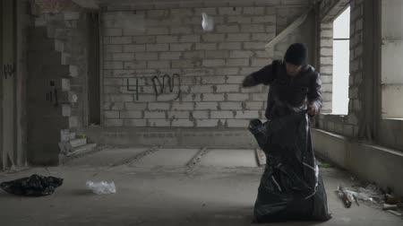 unlucky : Homeless man searches something in garbage bag Stock Footage