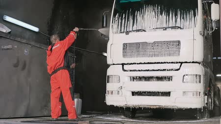 грузовик : Worker in protective overalls washes truck with water in slowmotion