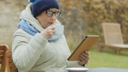 hot news : Granny in glasses uses tablet and drinks coffee relaxing in outdoors cafe