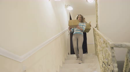 deslocalização : Married couple with boxes down the stairs and relocates from house