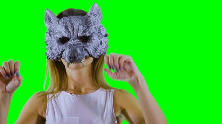 arranhão : Gilr wearing wolf mask scratches at green background Vídeos