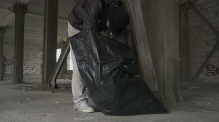 unlucky : Dirty bum searches something in garbage bag