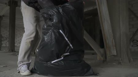 csavargó : Bald homeless searches something in garbage bag