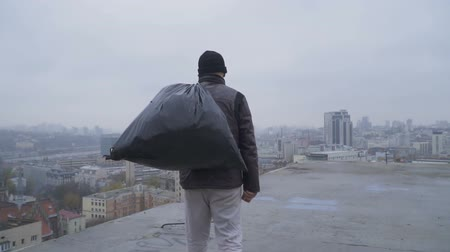 necessity : Homeless with garbage bag walks at the roof of abandoned building Stock Footage