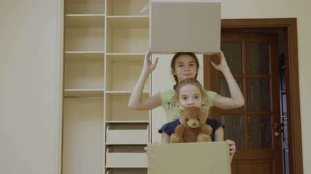 deslocalização : Two happy girls with boxes relocates in a new house