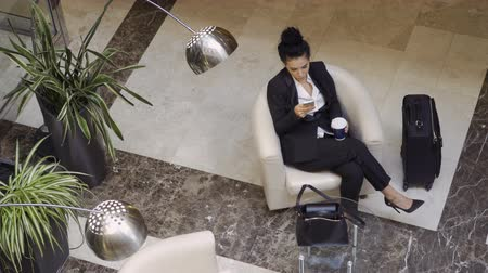 lobi : Beautiful business lady drinks coffee and uses phone in a lobby hall