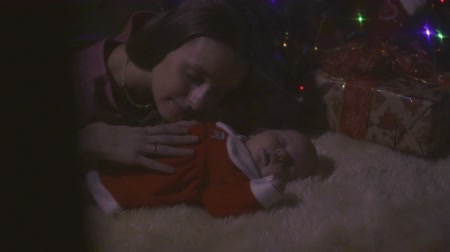 nascido : Young mother kisses her little sleeping daughter near Christmas tree Stock Footage